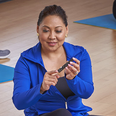 Woman lancing finger with Accu-Chek FastClix lancing device while doing yoga