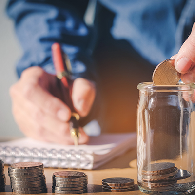 Man placing stacks of coins in an empty jar while marking in a spiral bound notepad with a ballpoint pen