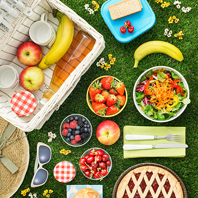Picnic lunch on lush green grass, featuring cherries, raspberries, strawberries, blueberries, bananas, apples, and salad