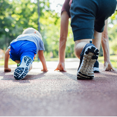 Father and son crouch in runner's stance ready to race each other down an empty suburban street