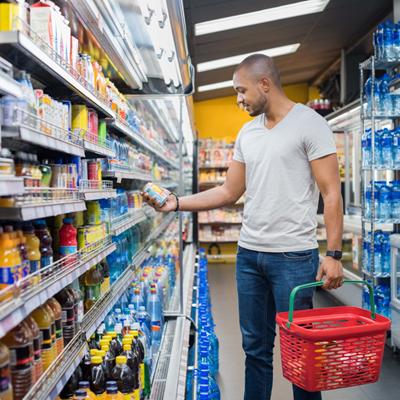Man perusing bottled beverages in empty supermarket aisle
