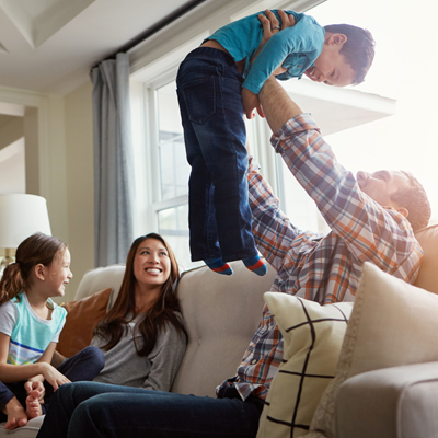 Father lifting small son skyward as he sits on the couch with smiling mother and daughter