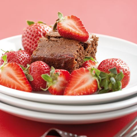 Luscious chocolate cake loaded with fresh strawberries on a white dessert plate
