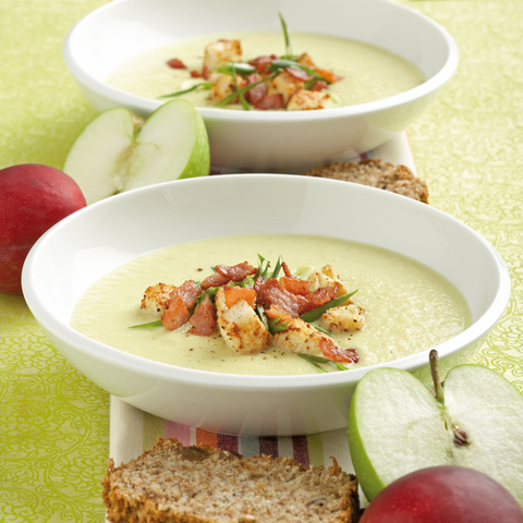 Image of a bowl cauliflower soup with croutons, surrounded by green and red apple slices