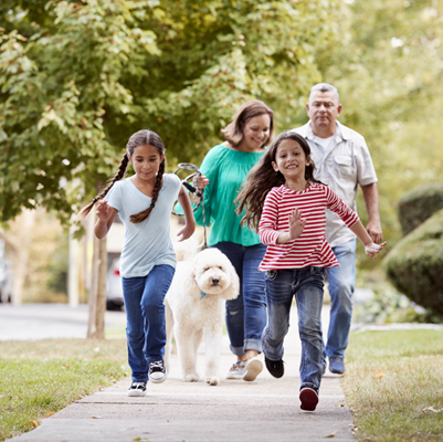 Smiling family of four walking down sidewalk with two young daughters running in front of parents walking dog