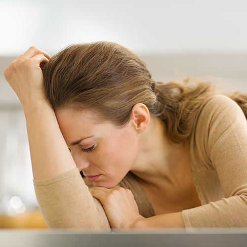 Stressed young woman leaning her head atop her hands in contemplation