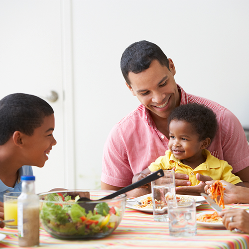 Family of four enjoying healthy meal together