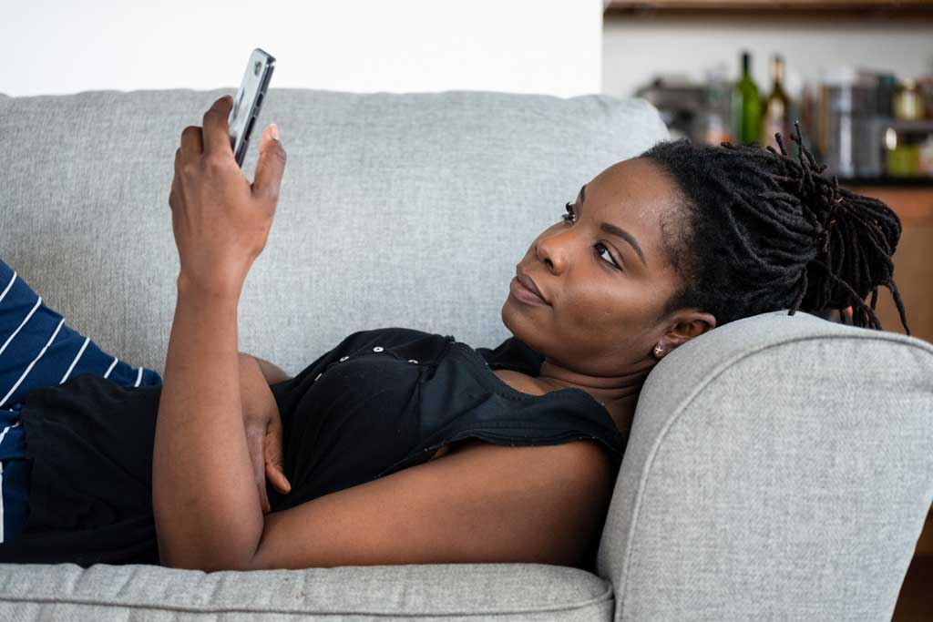 Picture of a lady using a mobile phone while laying on the couch.