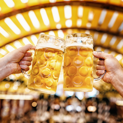 Two mugs of amber beer being raised in a toast