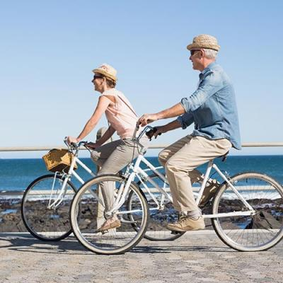 Elderly couple riding bikes alongside a tranquil bay of water