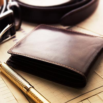 A solitary brown leather wallet sits atop a crowded desk next to a golden pen