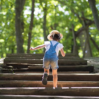 Adventurous young girl racing up stairs along a woodland trail