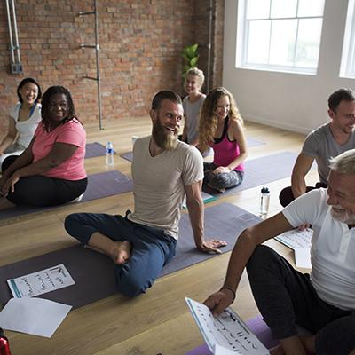 Yoga class with a wide variety of men and women on yoga mats