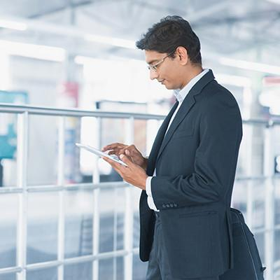 Businessman examining tablet computer while waiting in train station