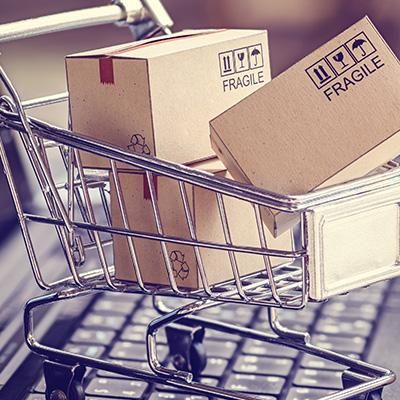 Brown shipping boxes piled high in shopping cart atop computer keyboard