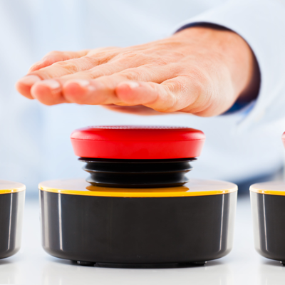 Expectant hand hovering inches above a trio of large red buttons