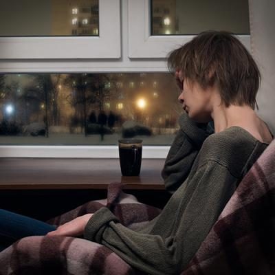 Stressed woman with coffee holds hand to her head as she looks out upon a cold, dark night
