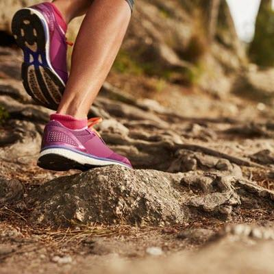 Woman's foot in pink running shoe hiking along rocky wilderness trail