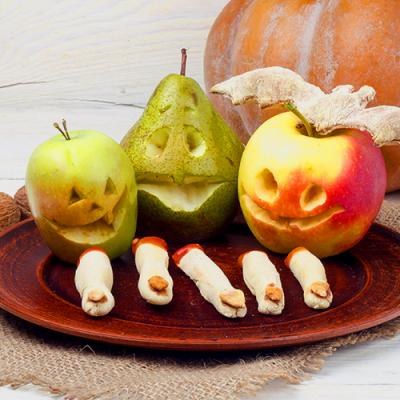 Two apples and a pear carved in the likeness of a jack-o-lantern