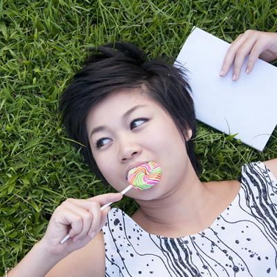 Woman lying on grassy field enjoying a lollipop