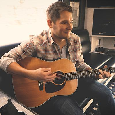 Country musician Ben Rue strumming an acoustic guitar while sitting inside his tour bus