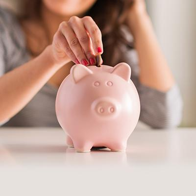 Woman placing coins in a pink piggy bank