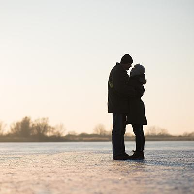 Couple in heavy winter attire kissing in the middle of a snowy, frozen field