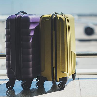Yellow and purple suitcases sitting beside each other in an airport