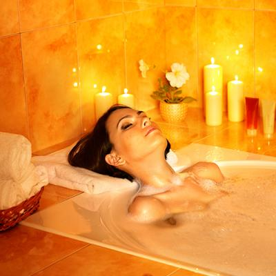 Young woman relaxing in soothing bubble bath, surrounded by lit candles