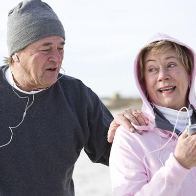 Elderly couple dressed for cold weather jogging while wearing earphones
