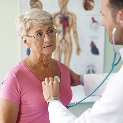 Doctor checking elderly woman's heartbeat during physician visit