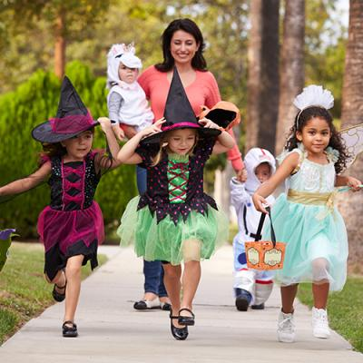 Woman chaperoning group of small children in Halloween costumes, including two witches,a fairy, a unicorn, and an astronaut