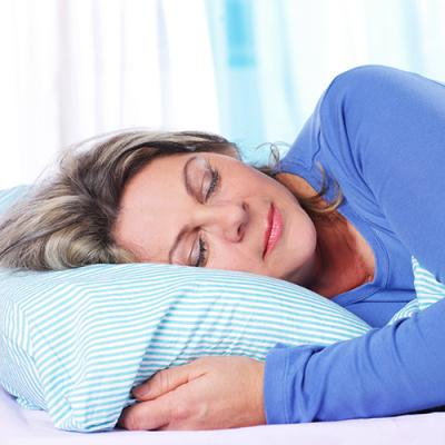 Woman blissfully sleeping in bed under covers