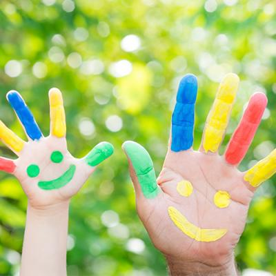 A child's hand and an adult's hand, both painted in bright colors along each finger with a smiley face on the palms
