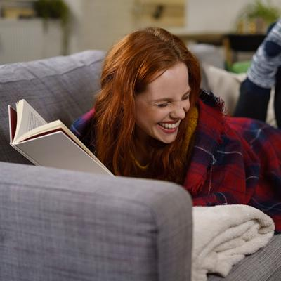 Red-haired young woman on a couch laughing while reading a book
