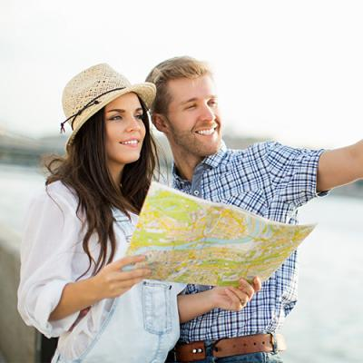 Couple dressed in vacation wear holding map and looking off expectantly in the distance