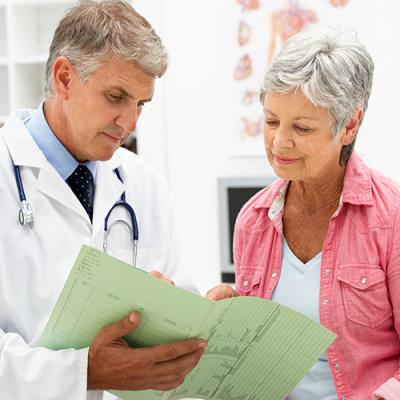 Elderly physician holding folder and discussing results with elderly female patient
