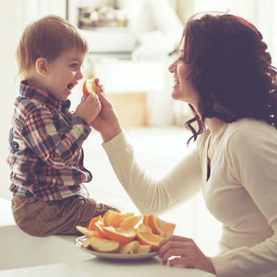 Mother handing an orange slice to her young son from plate laden with apple and orange slices