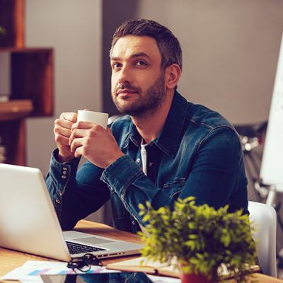Man at laptop drinking coffee and looking pensively towards a bright future