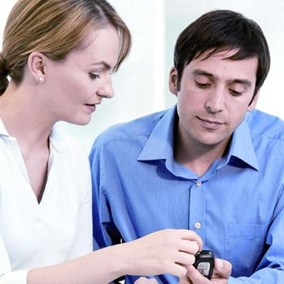 Woman explaining how to use a blood glucose meter to an attentive young man