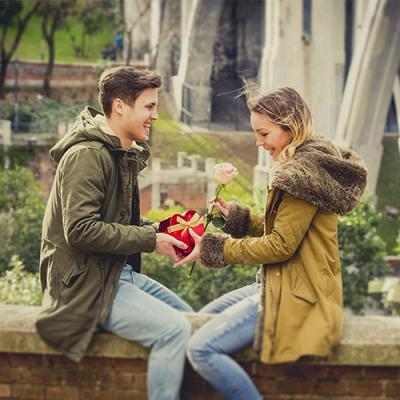 Young couple happily exchanging a heart-shaped chocolates box and a pink rose in a scenic park