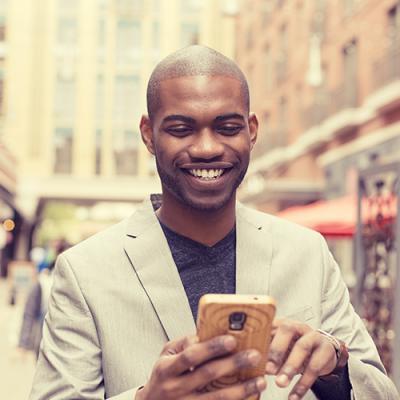 Smiling man using smartphone while walking down a crowded urban sidewalk