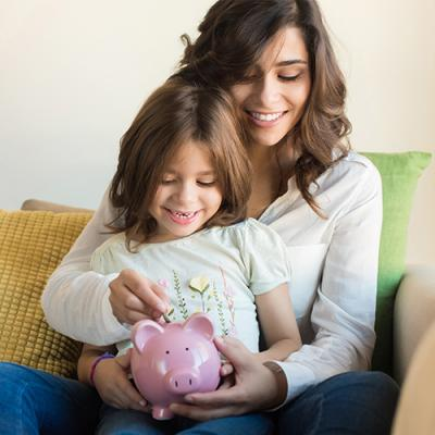 Mother with young daughter on lap placing coins in pink piggy bank