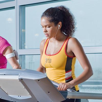 Young woman wearing earphones jogging on treadmill next to three other women on treadmills