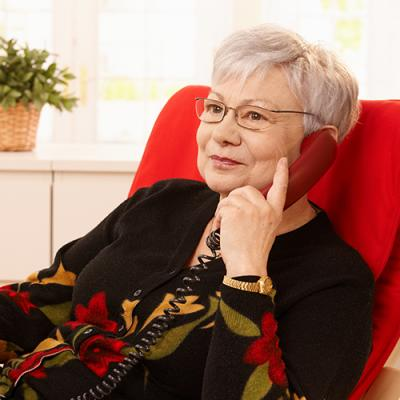 Elderly woman sitting on red chair patiently waiting on the phone