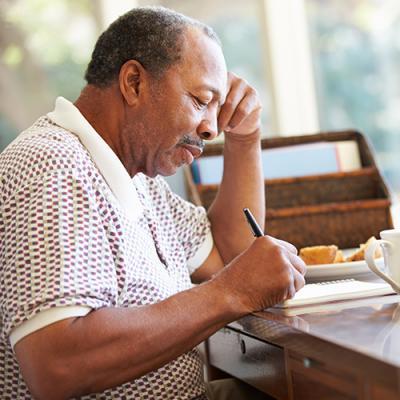 Elderly man at desk marking in a notebook with a ballpoint pen