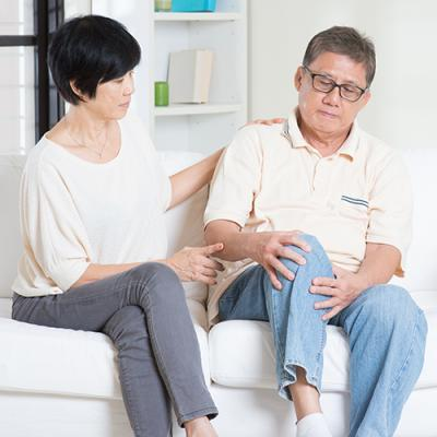 Seated man with a strained look on his face grabs questioningly at his knee while his wife places a hand on his shoulder