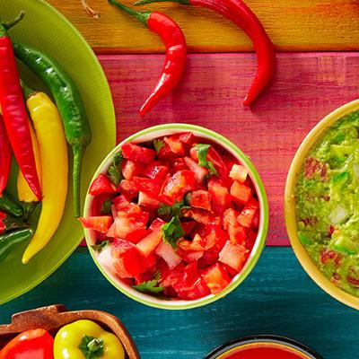 Colorful table loaded with bowls of diced tomatoes, guacamole, and assorted peppers
