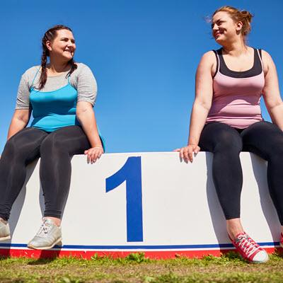 Two smiling women in exercise clothes atop winner's podium