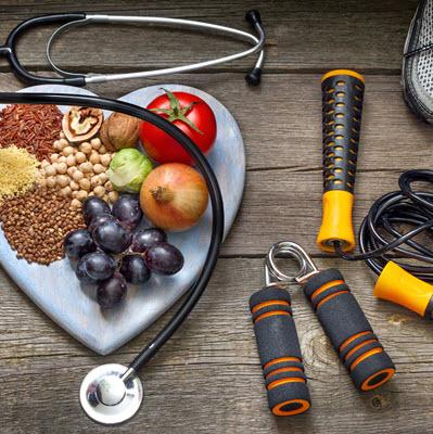 Heart-shaped platter of fresh fruit, vegetables, nuts, and grains surrounded by a jump rope, sneakers, a hand strengthener, and a stethoscope